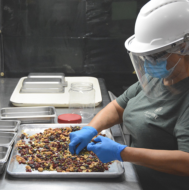 Plant worker sorting and doing quality assurance on trail mix