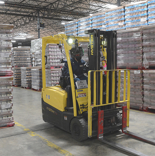Forklift and forklift driver in plant warehouse