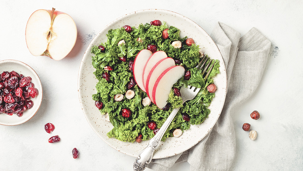 Kale salad in a bowl with dried cranberry, hazelnuts and sliced apple