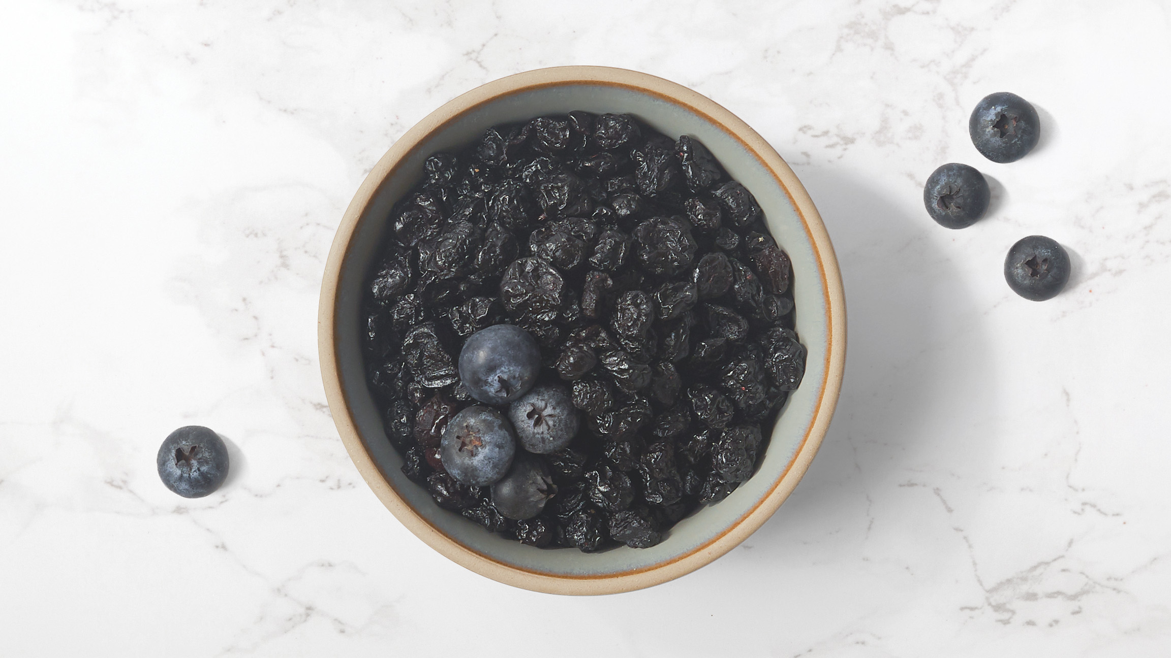 Dried blueberries in a ceramic bowl with fresh blueberries scattered on a marble counter