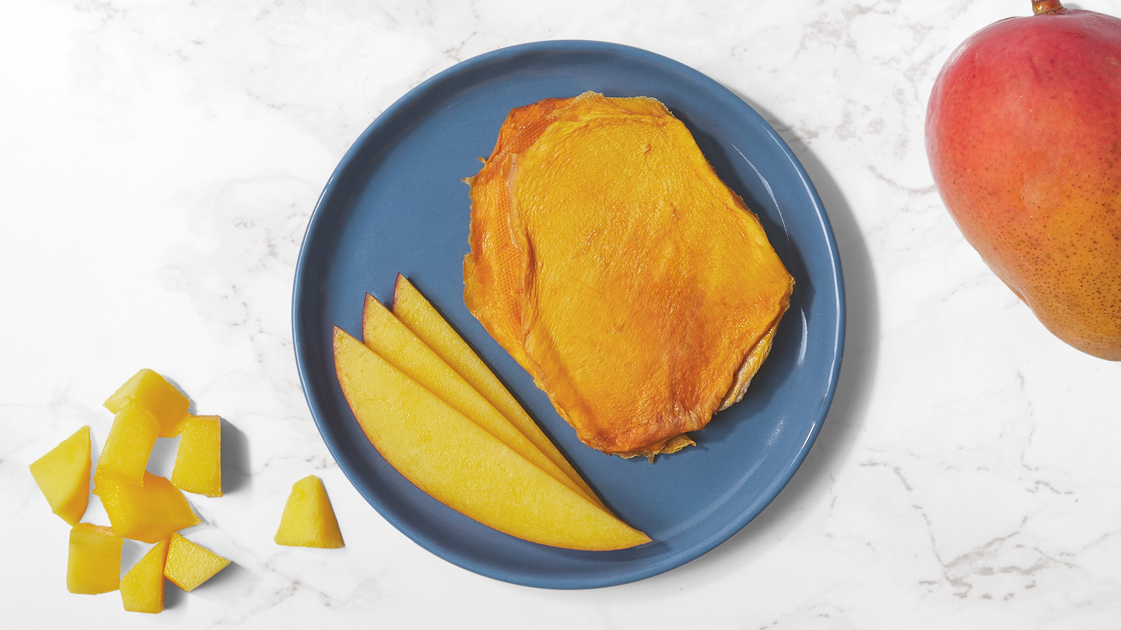 Dried and fresh mango slices on a blue plate with fresh pieces of mango and a whole mango on a white marble counter top