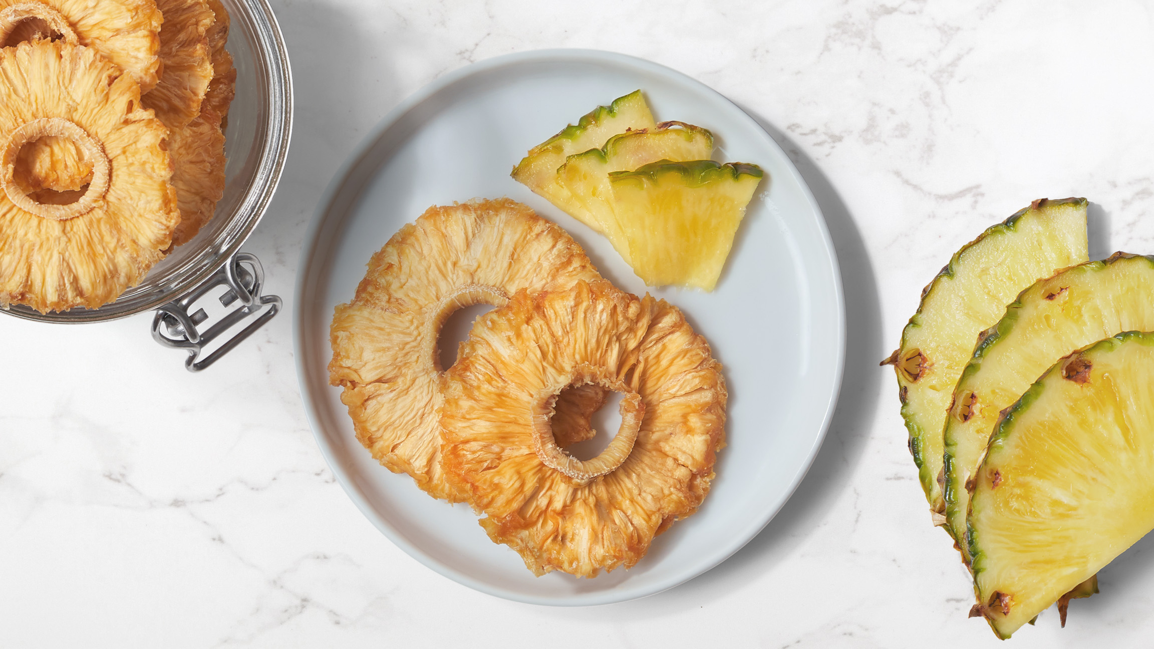 Dried pineapple rings and fresh pineapple slices on a white plate with fresh pieces of pineapple and a jar of dried pineapple rings on a white marble counter top