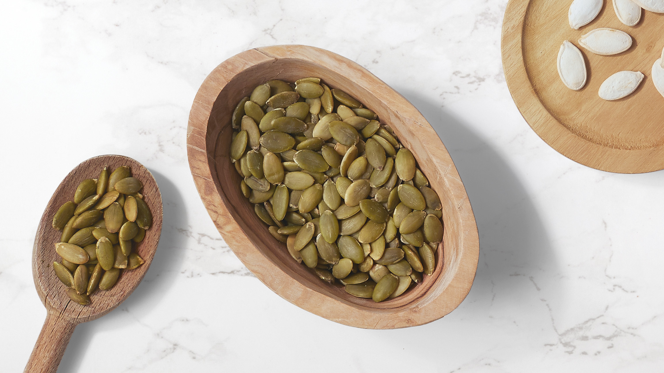 Pumpkin seeds in a wooden oval bowl accompanied with a wooden spoonful of pumpkin seeds on a white marble counter top