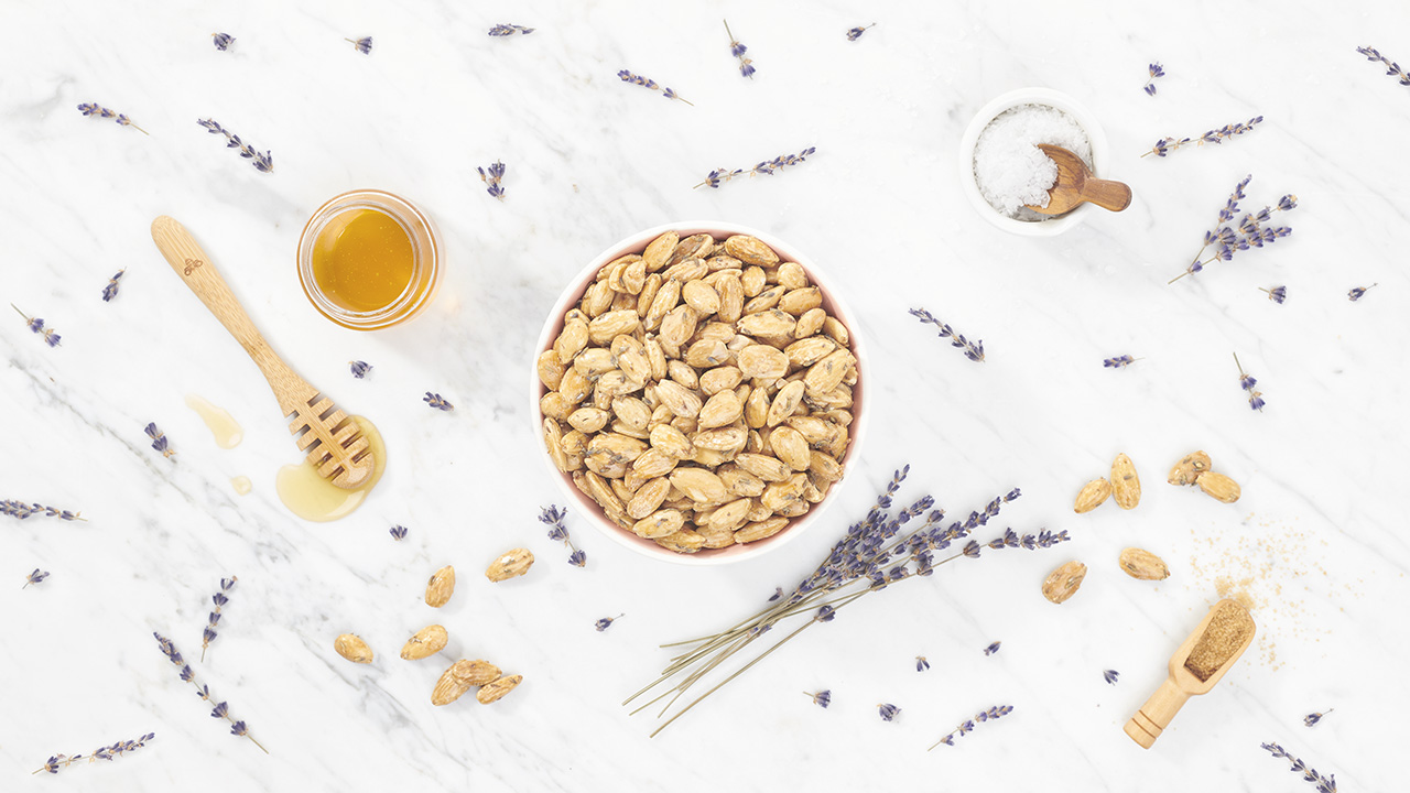 lavender honey almonds on a marble table with scattered ingredients
