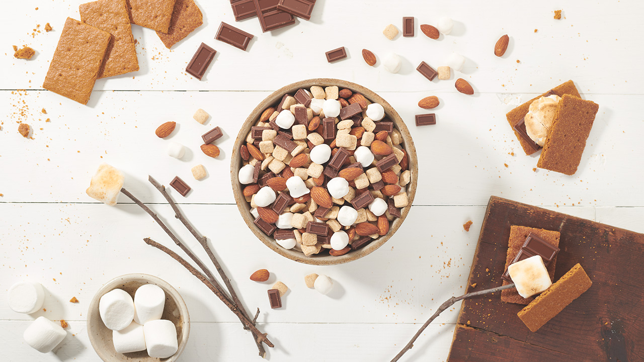 Bowl of S'more trail mix surrounded by scattered almonds, marshmallows, chocolate pieces and graham cracker pieces on a tabletop